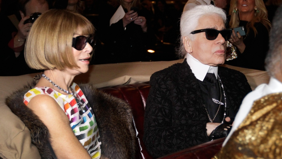 In this Tuesday, Dec. 10, 2013 file photo, Anna Wintour, left, the english editor-in-chief of American Vogue and designer Karl Lagerfeld sit in a vintage car as they wait to view a movie short of Coco Chanel's return to fashion after closing her house during WWII before the start of Chanel's Metiers d'Art fashion show, in Dallas.  (AP Photo/Tony Gutierrez, File)