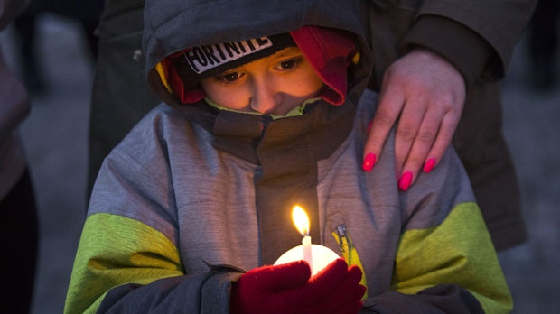 Six-year-old Mateo Escate stands with his mother Stephanie Escate during candlelight vigil held for Riya Rajkumar in Brampton, Ontario on Tuesday 19, 2019. Community members gathered in Brampton tonight to honour the 11-year-old girl allegedly killed by her father. THE CANADIAN PRESS/Chris Young