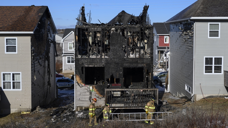 Firefighters investigate following a house fire in the Spryfield community in Halifax on Tuesday, February 19, 2019. Dozens of people gathered outside the charred remnants of a suburban Halifax home Tuesday night to mourn the loss of seven children killed in a fast-moving fire and to show support for the injured, grieving parents left behind. THE CANADIAN PRESS/Darren Calabrese