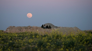 The moon rises behind U.S.-backed Syrian Democratic Forces (SDF) fighters at a defense post in the desert near the last land still held by Islamic State militants outside Baghouz, Syria, Tuesday, Feb. 19, 2019. The Islamic State group has been reduced from its self-proclaimed caliphate that once spread across much of Syria and Iraq at its height in 2014 to a speck of land on the countries' shared border. (AP Photo/Felipe Dana)