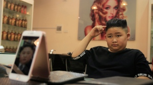 To Gia Huy, 9, checks his hair after having a Kim Jong Un haircut in Hanoi, Vietnam, on Tuesday, Feb. 19, 2019.  U.S. President Donald Trump and North Korean leader Kim Jong Un have become the latest style icons in Hanoi, a week before their second summit is to be held in the capital city of Vietnam.(AP Photo/Hau Dinh)