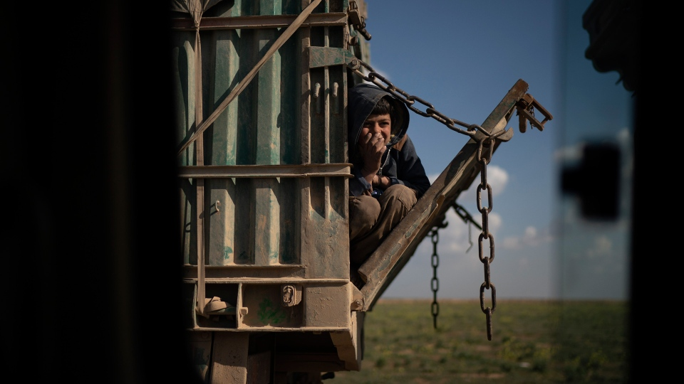 A boy rides in the back of a truck that is part of a convoy evacuating hundreds out of the last territory held by Islamic State militants, in Baghouz, eastern Syria, Wednesday, Feb. 20, 2019. (AP Photo/Felipe Dana)
