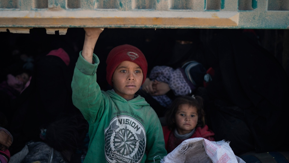 Children ride in the back of a truck that is part of a convoy evacuating hundreds out of the last territory held by Islamic State militants, in Baghouz, eastern Syria, Wednesday, Feb. 20, 2019. (AP Photo/Felipe Dana)
