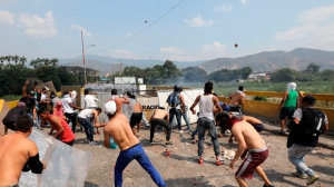 Venezuelan youth throws stones at a members of the Venezuela's National Guard on the Simon Bolivar international bridge in Cucuta, Colombia, Saturday, Feb. 23, 2019. The National Guard fired tear gas on opposition activists at the barricaded border bridge to Colombia on Saturday, and two protesters were killed near the border in Brazil, as the opposition tried to execute a high-risk plan to deliver humanitarian aid over the obstinate refusal of President Nicolas Maduro. (AP Photo/Fernando Vergara)