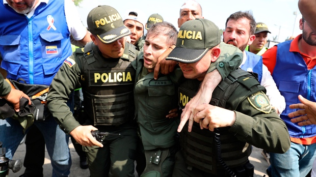 Colombian police escort a Venezuelan soldier who surrendered at the Simon Bolivar international bridge, where Venezuelans tried to deliver humanitarian aid despite objections from President Nicolas Maduro, in Cucuta, Colombia, Saturday, Feb. 23, 2019. Opposition leader Juan Guaido says the military is key to restoring democracy in Venezuela, although masses of soldiers appear to remain loyal to Maduro.  (AP Photo/Fernando Vergara)