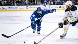 Toronto Maple Leafs centre Nic Petan (19) reaches for the puck as Buffalo Sabres defenceman Zach Bogosian (4) pressures in second period NHL hockey action in Toronto on Saturday, March 2, 2019. THE CANADIAN PRESS/Christopher Katsarov