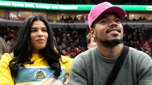 In this Nov. 26, 2018 file photo, Chance the Rapper, right, and Kirsten Corley appear during the second half of an NBA basketball game between the Chicago Bulls and the San Antonio Spurs in Chicago. The Chicago-based rapper tied the knot with Corley. He posted photos on his Instagram and Twitter accounts on Monday, March 11, 2019. (AP Photo/David Banks, File)