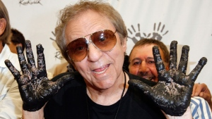 In this June 25, 2008, file photo, Hal Blaine holds up his hands covered in cement after placing them in wet cement with Don Randi and Glen Campbell, representing The Wrecking Crew following an induction ceremony for Hollywood's RockWalk in Los Angeles. (AP Photo/Kevork Djansezian, File)