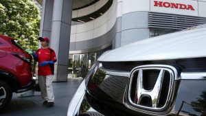 In this July 31, 2018 file photo, an employee of Honda Motor Co. cleans a Honda car displayed at its headquarters in Tokyo. (AP Photo/Koji Sasahara, File)