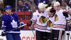 Chicago Blackhawks left wing Alex DeBrincat (12) celebrates his goal with teammates Chicago Blackhawks left wing Brendan Perlini (11) and Chicago Blackhawks left wing Brendan Perlini (11) as Toronto Maple Leafs defenceman Nikita Zaitsev (22) skates pass during second period NHL hockey action in Toronto on Wednesday, March 13, 2019. THE CANADIAN PRESS/Frank Gunn