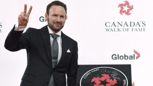 Singer Corey Hart stands beside his star as he is inducted into Canada's Walk of Fame in Toronto on Thursday, October 6, 2016. Hart is being inducted into the Juno Hall of Fame. THE CANADIAN PRESS/Nathan Denette
