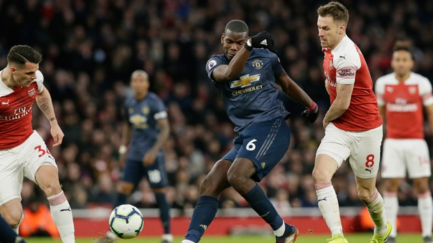 Manchester United's Paul Pogba kicks the ball ahead of Arsenal's Aaron Ramsey, right, and Arsenal's Granit Xhaka, left, during the English Premier League soccer match between Arsenal and Manchester United at the Emirates Stadium in London, Sunday, March 10, 2019. (AP Photo/Tim Ireland)