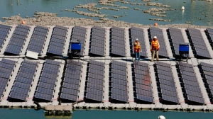 Workers stand on a floating island of solar panels on a pond at Los Bronces mine, about 65 kilometers (approximately 40 miles) from Santiago, Chile, Thursday, March 14, 2019. The 1,200-square-foot array of solar panels was inaugurated Thursday by Chilean Mining Minister Baldo Prokurica. Officials said that if the test is successful, the $250,000 plant could be expanded to cover 40 hectares, or nearly 100 acres. (AP Photo/Esteban Felix)
