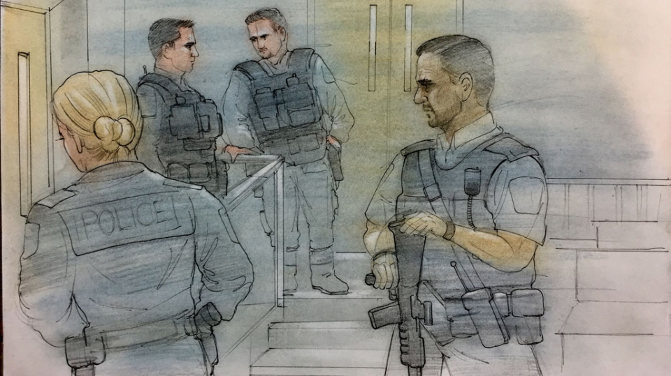 Heavily-armed Peel Regional Police tactical officers accompany two suspects to a Brampton courtroom on March 15, 2019. (John Mantha)