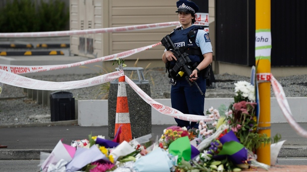 Police stand by a collection of flowers near the Linwood Mosque in Christchurch, New Zealand, Saturday, March 16, 2019, where one of the two mass shootings occurred. (AP Photo/Mark Baker)