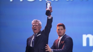 David Foster hoists the Juno for the Humanitarian of the Year with presenter Michael Buble at the Juno Gala Dinner and Awards in London, Ontario, Saturday, March 16, 2019. THE CANADIAN PRESS/ Geoff Robins