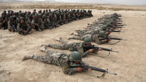 In this Oct. 31, 2018, photo, Afghan National Army soldiers carry out an exercise during a live firing at the Afghan Military Academy in Kabul, Afghanistan. (AP Photo/Rahmat Gul, File)
