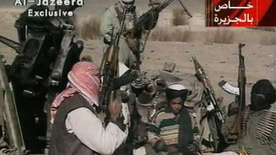 In this Nov. 5, 2001 image made from video broadcast by the Qatari-based television station Al-Jazeera, a young boy, center, identified as Hamza bin Laden, reads a poem about Taliban leader Mullah Mohammad Omar in Ghazni, Afghanistan. (AP Photo/Al-Jazeera via APTN, File)