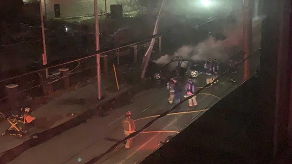 Firefighters extinguish a car fire after a vehicle struck a light standard on King Street East, near Parliament Street, Sunday March 17, 2019. (@mrriecker/ Twitter)