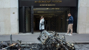 Bystanders walks past charred motorcycles on the Champs Elysees, the day after they were set on fire during the 18th straight weekend of demonstrations by the yellow vests, in Paris, France, Sunday, March 17, 2019.  (AP Photo/Rafael Yaghobzadeh)