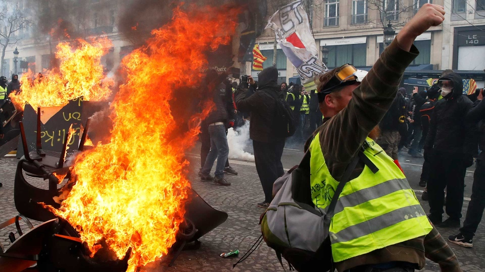 A protester shouts slogans in front of a barricade on fire during a yellow vests demonstration Saturday, March 16, 2019 in Paris. Paris police say more than 100 people have been arrested amid rioting in the French capital by yellow vest protesters and clashes with police. They set life-threatening fires, smashed up luxury stores and clashed with police firing tear gas and water cannon (AP Photo/Christophe Ena)