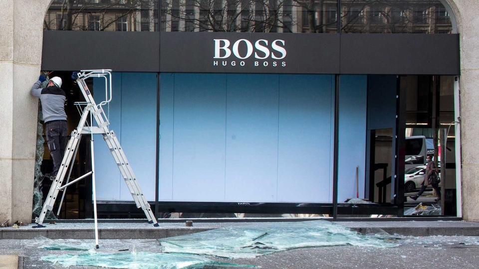 A worker repairs the shop windows of a clothing store on the Champs Elysees the day after it was vandalized during the 18th straight weekend of demonstrations by the yellow vests, in Paris, France, Sunday, March 17, 2019.  (AP Photo/Rafael Yaghobzadeh)