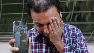 A relative weeps while showing the picture of Sohail Shahid, a Pakistani citizen who was killed in Christchurch mosque shootings, on his cell phone outside his home in Lahore, Pakistan, Sunday, March 17, 2019. (AP Photo/K.M. Chaudary)