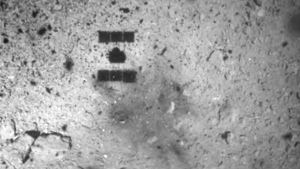 In this Feb. 22, 2019, file photo, this image released by the Japan Aerospace Exploration Agency (JAXA) shows the shadow, center above, of the Hayabusa2 spacecraft after its successful touchdown on the asteroid Ryugu. (JAXA via AP, File)