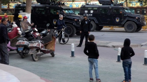 In this Nov. 5, 2017, file photo, residents watch a convoy of security personnel and armored vehicles in a show of force through central Kashgar in western China's Xinjiang region. (AP Photo/Ng Han Guan, File)