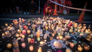 Mourners light candles, paying respects to the victims of Friday's shooting, outside the Al Noor mosque in Christchurch, New Zealand, Monday, March 18, 2019.  (AP Photo/Vincent Thian)