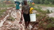 People trudge through a muddied path to safer ground in Chimanimani, about 600 kilometers southeast of Harare, Zimbabwe, Monday, March 18, 2019. (AP Photo/Tsvangirayi Mukwazhi)