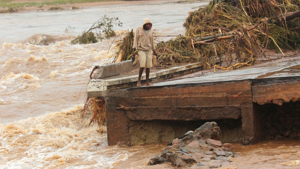 A man stands on the edge of a collapsed bridge in Chimanimani, about 600 kilometers southeast of Harare, Zimbabwe, Monday, March 18, 2019. (AP Photo/Tsvangirayi Mukwazhi)