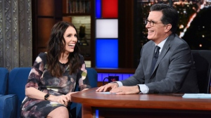 "This Sept. 26, 2018 photo release by CBS shows New Zealand Prime Minister Jacinda Ardern, left, with host Stephen Colbert during a taping of ""The Late Show with Stephen Colbert,"" in New York. Colbert has postponed what was supposed to be a surprise visit to New Zealand following the terrorist attack in Christchurch that killed 50 people. Colbert's The top-rated American late-night show said that he was supposed to travel to New Zealand on Wednesday for a week of shows. He was invited last fall when Ardern was a guest on the show. (Scott Kowalchyk/CBS via AP)"