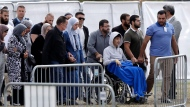 Zaed Mustafa, in wheelchair, brother of Hamza and son of Khalid Mustafa killed in the Friday March 15 mosque shootings arrives for the burial at the Memorial Park Cemetery in Christchurch, New Zealand, Wednesday, March 20, 2019. (AP Photo/Mark Baker)