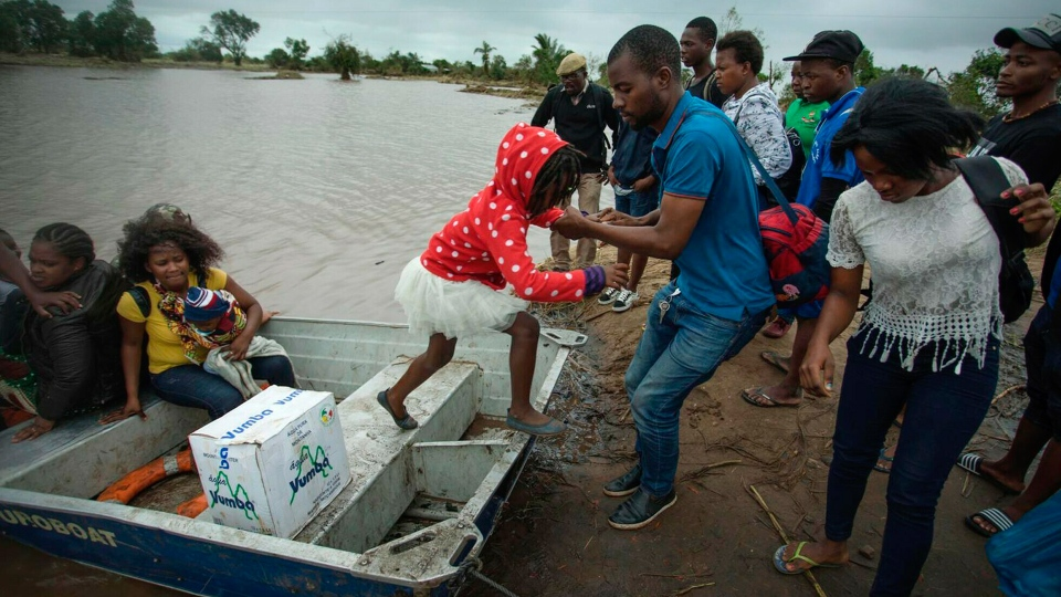 A young girl is helped from a boat after being evacuated from flood waters following cyclone force winds and heavy rain near the coastal city of Beira, Mozambique, Wednesday March 20, 2019.  (Josh Estey/CARE via AP)
