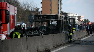 Firefighters stand by the gutted remains of a bus in San Donato Milanese, near Milan, Italy, March 21, 2019. Italian authorities say a bus driver transporting schoolchildren stopped his vehicle on a provincial highway, told the passengers to get off and then doused the interior with gasoline and set it on fire. Italian media reported that the driver, an Italian of Senegalese origin, was immediately apprehended. (Daniele Bennati/ANSA via AP)