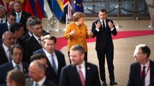 German Chancellor Angela Merkel, center left, speaks with French President Emmanuel Macron, center right, prior to a group photo at an EU summit in Brussels, Friday, March 22, 2019. European Union leaders gathered again Friday after deciding that the political crisis in Britain over Brexit poses too great a threat and that action is needed to protect the smooth running of the world's biggest trading bloc. (AP Photo/Francisco Seco)