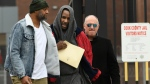 In this March 9, 2019 photo, singer R. Kelly center, walks with his attorney Steve Greenberg right, and an unidentified man left, who gave him a ride after being released from Cook County Jail, March 9, 2019, in Chicago. A Chicago judge is expected to rule on whether to let R. Kelly to travel overseas to perform several concerts to help the cash-strapped singer pay legal and other bills as he faces sex-abuse charges. A hearing Friday, March 22, follows a defense motion saying the 52-year-old singer hopes to do up to five April concerts in Dubai. (AP Photo/Paul Beaty, File)