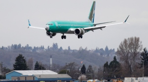 A Boeing 737 MAX 8 being built for Oman Air lands at Boeing Field, Friday, March 22, 2019, in Seattle. In a blow for Boeing, Indonesia's flag carrier is seeking the cancellation of a multibillion dollar order for 49 of the manufacturer's 737 Max 8 jets, citing a loss of confidence after two crashes within five months. (AP Photo/Ted S. Warren)