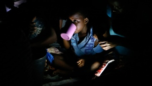 Displaced children, victims of Cyclone Idai, eat lunch at the Samora Machel Secondary School which is being used to house victims of the floods in Beira, Mozambique, Sunday March 24, 2019. . (AP Photo/Phill Magakoe)