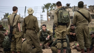 Israeli soldiers near the Israel Gaza border, Tuesday, March 26, 2019. A tense quiet took hold on Tuesday morning after a night of heavy fire as Israeli aircraft bombed targets across the Gaza Strip and Gaza militants fired rockets into Israel in what threatened to devolve into a major conflict, just two weeks before the Israeli election. (AP Photo/Tsafrir Abayov)