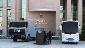 Security cars and an official stand outside the Justice Palace as a trial against Metin Topuz, a Turkish employee of the United States Consulate in Istanbul charged with espionage and attempting to overthrow the Turkish government, began in Istanbul, Tuesday, March 26, 2019. Topuz, a translator and fixer for the Drug Enforcement Agency at the consulate, will have his first hearing Tuesday. He has been in pre-trial detention since October 2017. (AP Photo/Mehet Guzel)