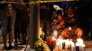 Haitian-French actor Jimmy Jean-Louis and his daughter Jasmin, 16, gather around candles set up across from the store of rapper Nipsey Hussle in Los Angeles, Sunday, March 31, 2019. Hussle, the skilled and respected West Coast rapper who had a decade-long success with mixtapes but hit new heights with his Grammy-nominated major-label debut album in 2018, has died. He was 33. (AP Photo/Damian Dovarganes)