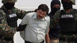 """In this Feb. 22, 2014, file photo, Joaquin """"El Chapo"""" Guzman is escorted to a helicopter in handcuffs by Mexican navy marines at a navy hanger in Mexico City, Mexico. The convicted drug lord and his wife have stylish future plans: Creating clothing with the brand name """"El Chapo."""" The New York Daily News reports on Friday, March 29, 2019, that 61-year-old Guzman and his 29-year-old wife, Emma Coronel Aispuro, are working together on the project. (AP Photo/Eduardo Verdugo, File)"""
