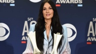"""Kacey Musgraves poses in the press room with the awards for album of the year for """"Golden Hour"""" and female artist of the year at the 54th annual Academy of Country Music Awards at the MGM Grand Garden Arena on Sunday, April 7, 2019, in Las Vegas. (Photo by Jordan Strauss/Invision/AP)"""