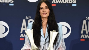 "Kacey Musgraves poses in the press room with the awards for album of the year for ""Golden Hour"" and female artist of the year at the 54th annual Academy of Country Music Awards at the MGM Grand Garden Arena on Sunday, April 7, 2019, in Las Vegas. (Photo by Jordan Strauss/Invision/AP)"