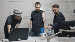 Lead Research Engineer Michale Rory Dawson, left, sets up a task for research participant Chris Neilson to perform with the Bento Arm, centre, while Patrick Pilarski, who is the Canada Research Chair in machine Intelligence for Rehabilitation, gives it a cup to hold at the University of Alberta's BLINC lab in Edmonton, Alberta, on Thursday March 14, 2019. THE CANADIAN PRESS/Amber Bracken