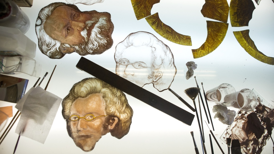 Details of the original stained glass portraits of the composers Franz Shubert and Charles Gounod, together with a newly produced layer of glass depicting Shubert, lie on a light table during restoration work on Massey Hall's 125-year-old stained glass windows at Toronto's EGD Glass & Vitreous Glassworks on Thursday, April 4, 2019. THE CANADIAN PRESS/Chris Young