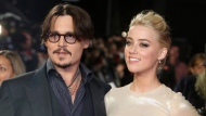 """In this Nov. 3, 2011 file photo, U.S. actors Johnny Depp, left, and Amber Heard arrive for the European premiere of their film, """"The Rum Diary,"""" in London.Heard is asking a judge to dismiss a $50 million defamation lawsuit her ex-husband Johnny Depp filed over a Washington Post op-ed she wrote about domestic violence. In the motion filed Thursday in Fairfax, Virginia, Heard's lawyers reiterate allegations that Depp abused her and include exhibits such as photos of her with bruised face and scarred arms. (AP Photo/Joel Ryan, File)"""