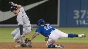 Tampa Bay Rays' Austin Meadows doubles in the ninth inning as Toronto Blue Jays' Freddy Galvis misses the tag during American League MLB baseball game in Toronto Friday April 12, 2019. THE CANADIAN PRESS/Fred Thornhill